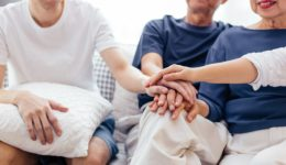family putting hands together and choosing the right hospice care program
